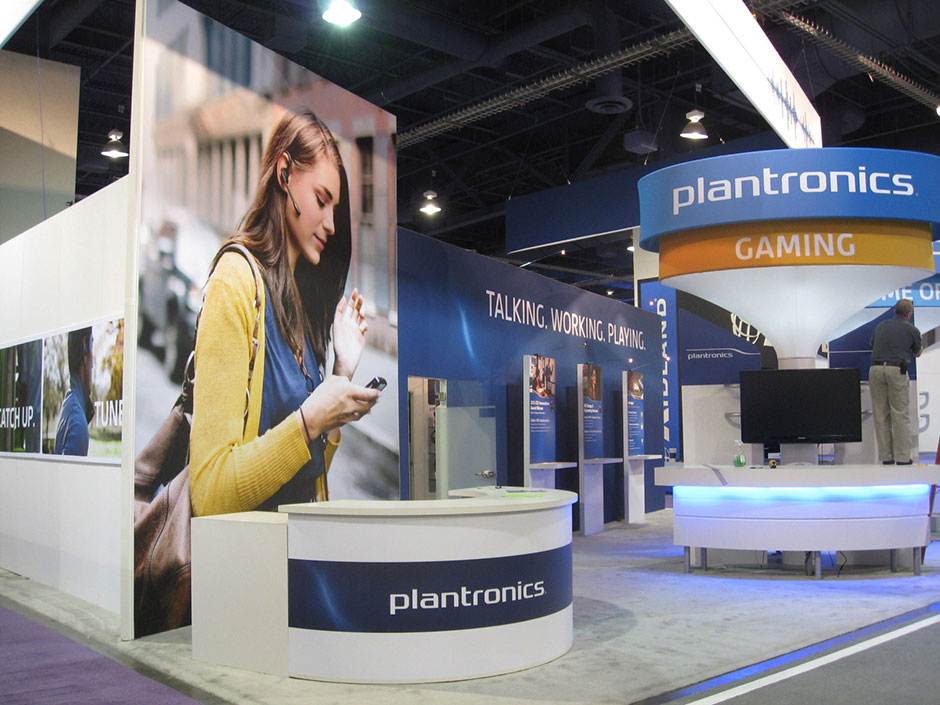 Booth front with registration desk, demo stations, and hero kiosks.